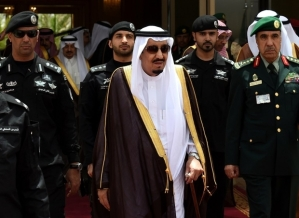 Saudi King Salman bin Abdulaziz (C) walks surrounded by security officers to receive Bahraini King Hamad bin Isa al-Khalifa (unseen) upon the latter's arrival in Riyadh to attend the Gulf Cooperation Council (GCC) summit on May 5, 2015. AFP PHOTO / FAYEZ NURELDINE