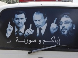 A poster showing Syrian President Bashar al-Assad (L), Russian President Vladimir Putin (C) and Lebanese Hezbollah leader Sayyed Hassan Nasrallah is seen on a micro bus in al-Qardahah town, near Latakia city May 26, 2014.  REUTERS/Khaled al-Hariri