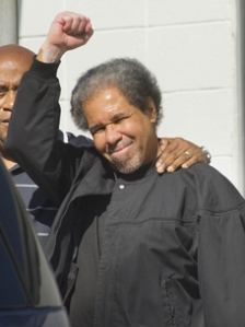 """Albert Woodfox, right, raises a clenched fist as he walks out of the West Feliciana Detention Center with his brother, Michael Mable, left, Friday, Feb. 19, 2016, in St. Francisville, La. Woodfox was released Friday after pleading no contest to manslaughter and aggravated burglary in the 1972 death of a prison guard. Woodfox and two other men became known as the """"Angola Three"""" for their decades-long stays in isolation at the Louisiana Penitentiary at Angola and other state prisons. (Travis Spradling/The Advocate via AP) MAGS OUT; INTERNET OUT; NO SALES; TV OUT; NO FORNS; LOUISIANA BUSINESS INC. OUT (INCLUDING GREATER BATON ROUGE BUSINESS REPORT, 225, 10/12, INREGISTER, LBI CUSTOM); MANDATORY CREDIT"""